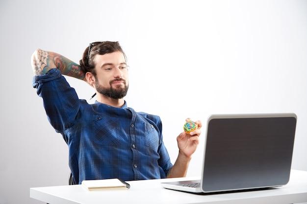 Atrakcyjny młody człowiek ubrany w niebieską koszulę siedzi z laptopem i pracy, pojęcie freelance, portret, myślenie.