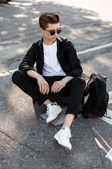 Atrakcyjny młody człowiek w eleganckiej koszuli w stylowych okularach przeciwsłonecznych