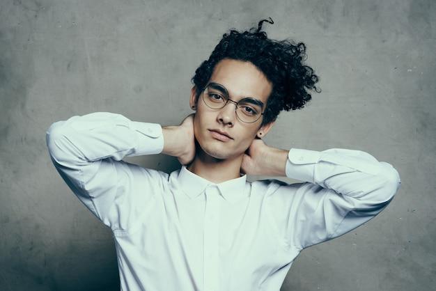 Atrakcyjny młody człowiek w okularach białą koszulę prostuje włosy na głowie