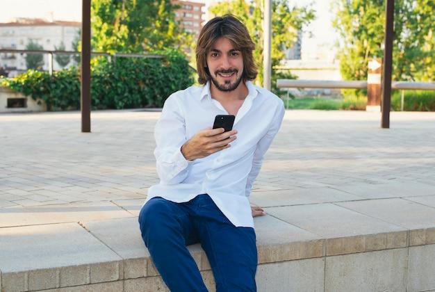 Atrakcyjny młody człowiek z brodą, z białą koszulą trzyma w ręku smartfon i jest w parku, uśmiecha się.