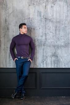 Atrakcyjny młody człowiek z rękami w kieszeni opierając się na betonowej szarej ścianie