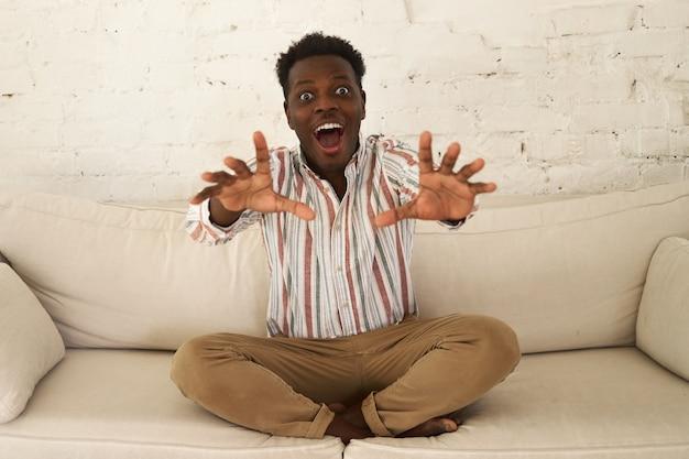 Atrakcyjny młody facet afro amerykanin podekscytowany i uszczęśliwiony