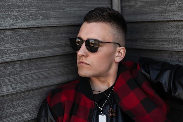 Atrakcyjny młody hipster mężczyzna w modnych czarnych okularach z modną fryzurą w stylowej czerwono-czarnej kraciastej kurtce ze skórzanymi rękawami przy drewnianej ścianie