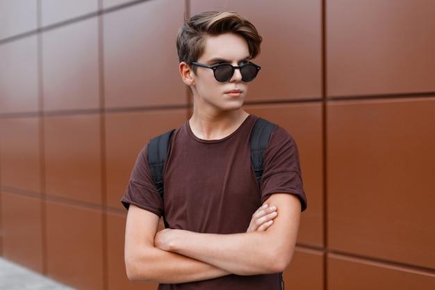 Atrakcyjny młody hipster mężczyzna w okularach przeciwsłonecznych w letniej koszulce z plecakiem sportowym stoi na ulicy w słoneczny dzień w pobliżu zabytkowego budynku