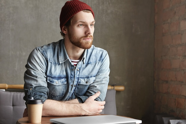 Atrakcyjny młody kaukaski hipster w stylowe ubrania o przemyślany marzycielski wygląd