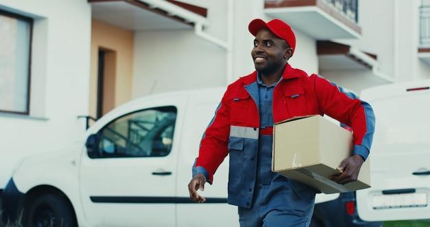 Atrakcyjny młody listonosz afroamerykanin w czerwonym stroju i czapce wyjmujący paczkę z furgonetki i idący do domu, aby ją dostarczyć. na dworze.