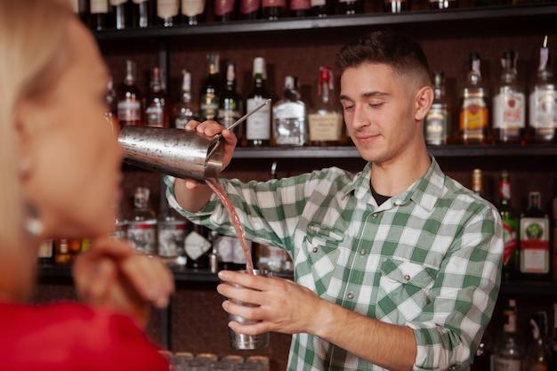 Atrakcyjny młody męski barman przygotowywa napój dla jego żeńskiego klienta