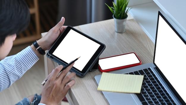 Atrakcyjny młody mężczyzna pracujący z wieloma elektronicznymi urządzeniami internetowymi w biurze.