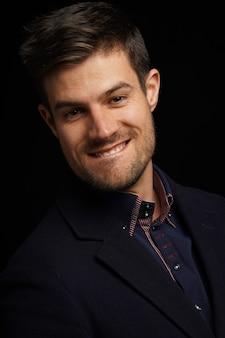 Atrakcyjny młody mężczyzna przygryzający wargę i flirtujący z kimś stojąc nad czarną ścianą