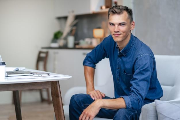 Atrakcyjny młody mężczyzna siedzi w krześle domowym.