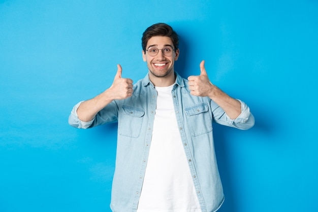 Atrakcyjny młody mężczyzna w okularach i ubraniu, pokazując kciuk do góry w aprobacie, jak coś, stojąc na niebieskim tle.