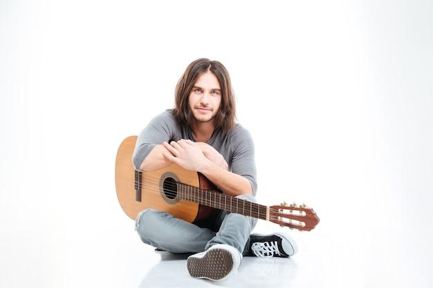 Atrakcyjny młody mężczyzna z długimi włosami siedzi i trzyma gitarę na białym tle