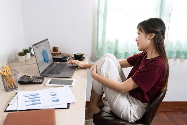 Atrakcyjny młody piękny azjatykci kobieta przedsiębiorca lub freelancer pracuje w domu z laptopów raportami biznesowymi i komunikacjami online na żywej izbowej kanapie, pracuje zdalnie dostępowego pojęcie.
