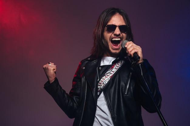 Atrakcyjny młody piosenkarz w okularach przeciwsłonecznych z długimi włosami śpiewa z mikrofonem na kolorowym zadymionym tle