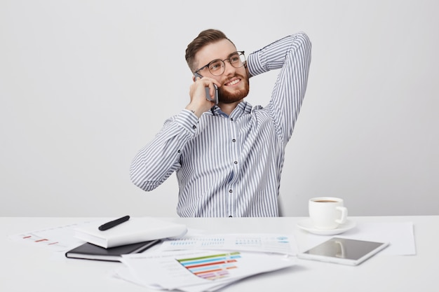 Atrakcyjny młody pracownik o atrakcyjnym wyglądzie ma przerwę na kawę, czuje się zrelaksowany