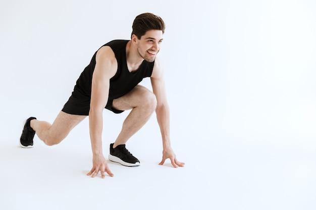 Atrakcyjny młody sportowiec przygotowuje się do biegu na białym tle