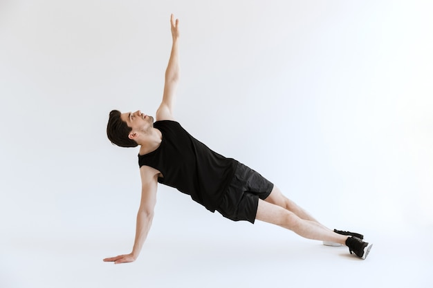 Atrakcyjny młody sportowiec robi ćwiczenia deski na białym tle