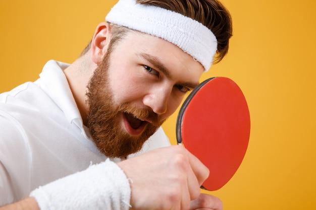 Atrakcyjny młody sportowiec trzyma rakietę do tenisa stołowego.