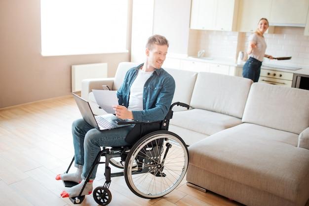 Atrakcyjny młody student z włączeniem i niepełnosprawnością. siedząc na krześle i oglądając się za siebie. młoda kobieta gotowania w piecu. spójrz na siebie. para w pokoju