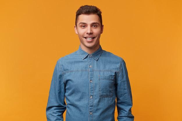 Atrakcyjny, młody, uroczy facet uśmiecha się przyjaźnie, pokazuje zdrowe zęby, ubrany w nową dżinsową koszulę, odizolowany na żółtej ścianie