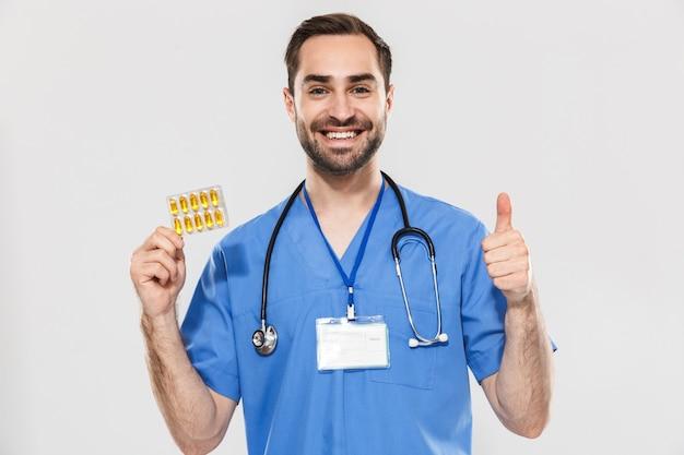 Atrakcyjny młody wesoły mężczyzna lekarz ubrany w mundur stojący na białym tle nad białą ścianą, pokazujący kapsułki z pigułkami