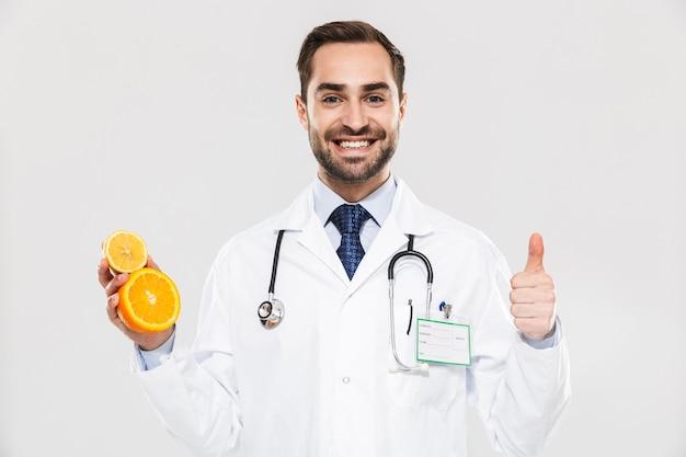 Atrakcyjny młody wesoły mężczyzna lekarz ubrany w mundur stojący na białym tle nad białą ścianą, pokazujący plasterki pomarańczy