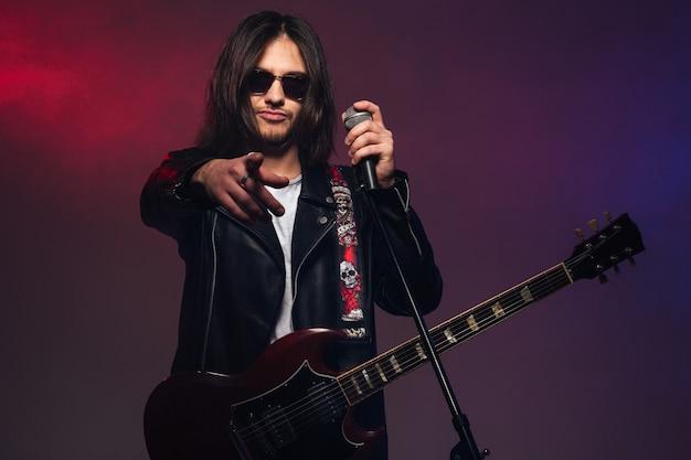 Atrakcyjny młody wokalista z gitarą trzymający mikrofon i wskazujący na ciebie na kolorowym zadymionym tle
