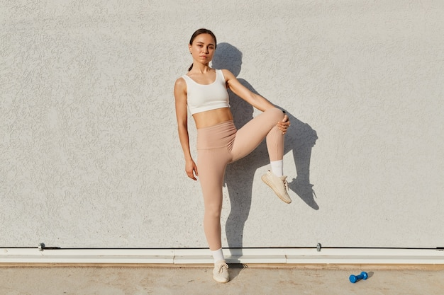 Atrakcyjny model fitness dziewczyna pozuje w pobliżu szarej ściany, ubrana w biały sportowy top i beżowe legginsy