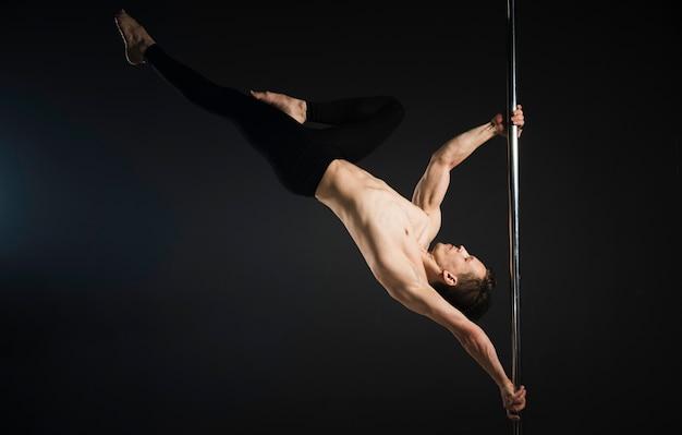 Atrakcyjny model mężczyzna wykonujący taniec na rurze