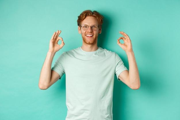 Atrakcyjny model mężczyzna z rudymi włosami, w okularach, pokazujący zgodę na znak ok i mówiący tak, uśmiechnięty zadowolony, stojący na miętowym tle.
