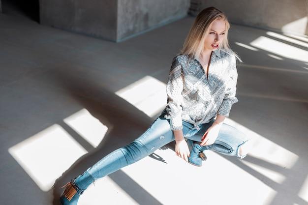 Atrakcyjny model modnej młodej kobiety w stylowe dżinsy w modnych kowbojskich butach w koszuli vintage pozowanie w pomieszczeniu, ciesząc się słońcem