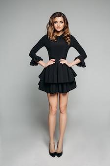Atrakcyjny model z brunatnymi falowanymi włosami w klasycznej fantazyjnej czarnej sukience i szpilkach.