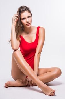 Atrakcyjny model z brunetką siedzi na podłodze ubrany w czerwony kostium kąpielowy na białym tle