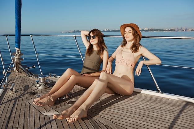 Atrakcyjny modny model w bikini opalający się na łodzi z zamkniętymi oczami i zadowolonym uśmiechem podczas żeglowania w morzu. przyjaciele postanowili ukryć się przed mroźną zimą i udać się na wyspy zwrotnikowe.