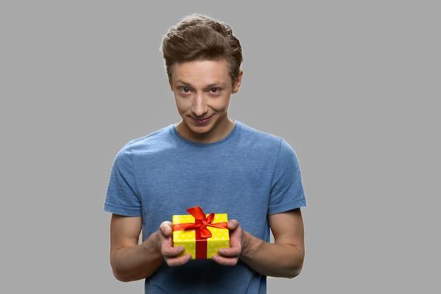 Atrakcyjny nastolatek chłopiec dając obecne pudełko. przystojny nastoletni facet trzymając pudełko na szarym tle. szczęśliwego dnia matki.
