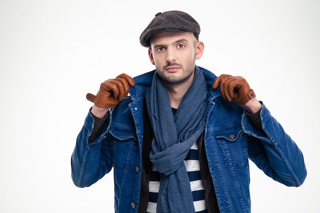 Atrakcyjny nowoczesny model mężczyzna pozuje w stylowych ubraniach na białej ścianie