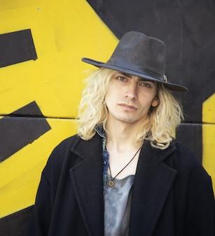 Atrakcyjny ormianin w kapeluszu na żółto-czarnej ścianie