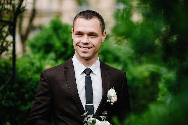 Atrakcyjny pan młody w garniturze i krawacie z butonierką lub butonierką na kurtce stoi na tle zieleni w ogrodzie, parku. natura.