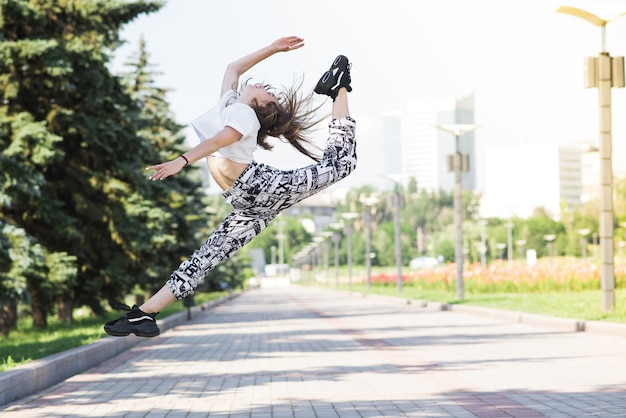 Atrakcyjny piękny kaukaski dziewczyna tańczy na ulicy. sport, taniec, kultura miejska. styl życia moda.