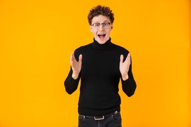 Atrakcyjny podekscytowany mężczyzna w okularach wyrażający niespodziankę na żółto