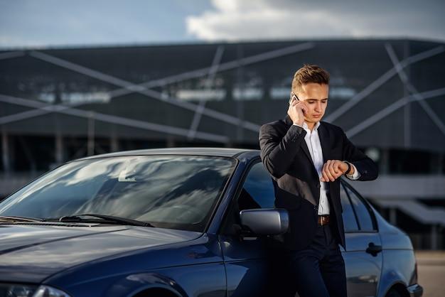 Atrakcyjny pomyślny młody biznesmen w garniturze i zegarek pod ręką opowiada na smartphone blisko jego samochodu