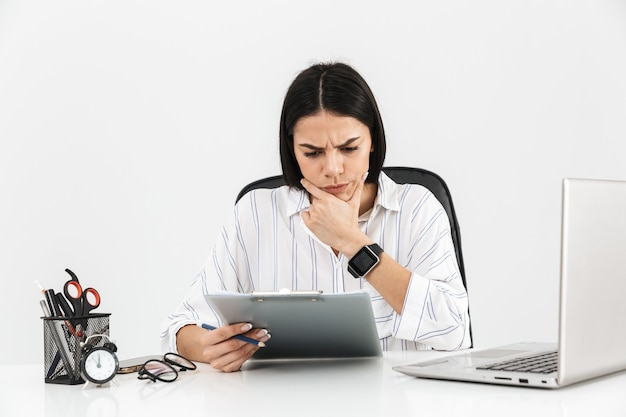 Atrakcyjny poważny młody bizneswoman siedzi przy biurku na białym tle nad białą ścianą