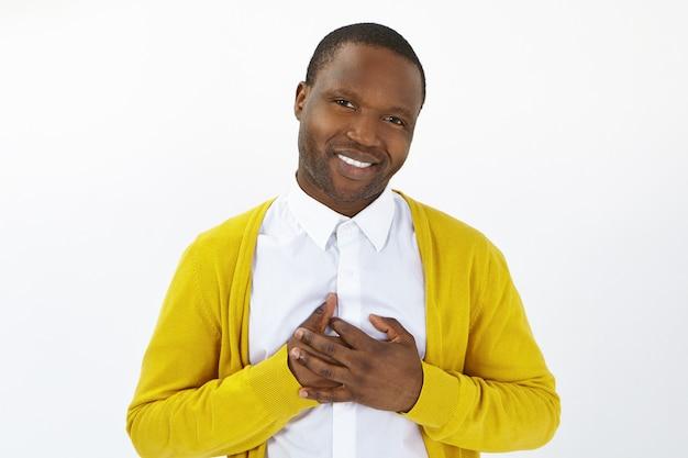 Atrakcyjny, pozytywny młody afro mężczyzna patrzy w kamerę z otwartym, pełnym uznania uśmiechem, trzymając ręce na piersi, okazując wdzięczność, czując wdzięczność za pomoc. ludzkie emocje, reakcje i uczucia
