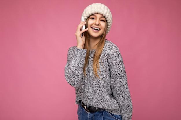 Atrakcyjny pozytywny szczęśliwy młoda blondynka ubrana dorywczo szary sweter i beżowy kapelusz na białym tle nad różowym tle, trzymając w ręku i mówiąc na telefon komórkowy, patrząc na kamery.