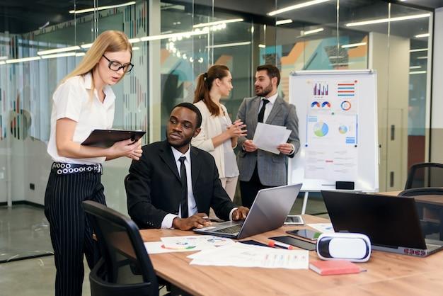 Atrakcyjny pracownik konsultuje się z kierownikiem biura i podpisuje dokument finansowy w swoim miejscu pracy.