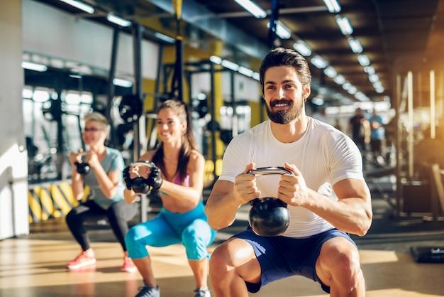Atrakcyjny przystojny brodaty mężczyzna trzyma kettlebell i robi przysiady w grupie fitness z dwiema dziewczynami w nowoczesnej siłowni.