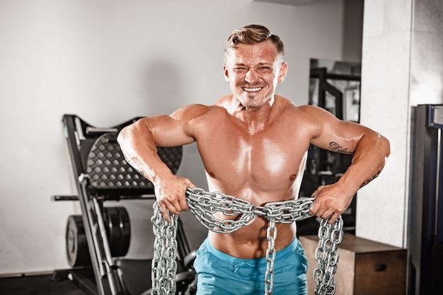 Atrakcyjny, przystojny, czarny mężczyzna kulturysta robi kulturystyce stanowią w siłowni z żelaznymi łańcuchami