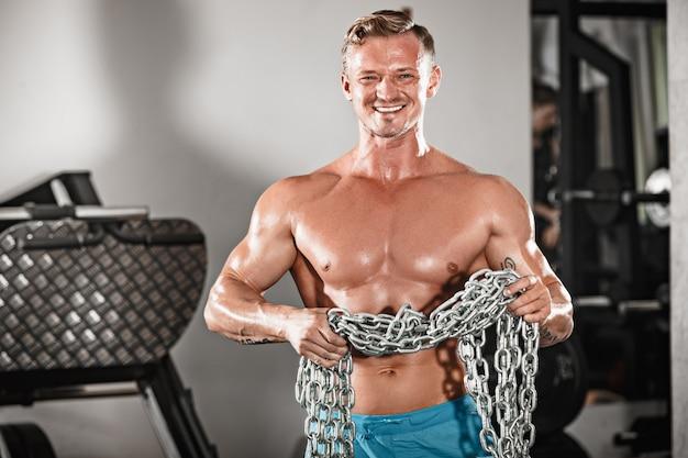 Atrakcyjny przystojny mężczyzna kulturysta robi kulturystykę pozie w siłowni z żelaznymi łańcuchami