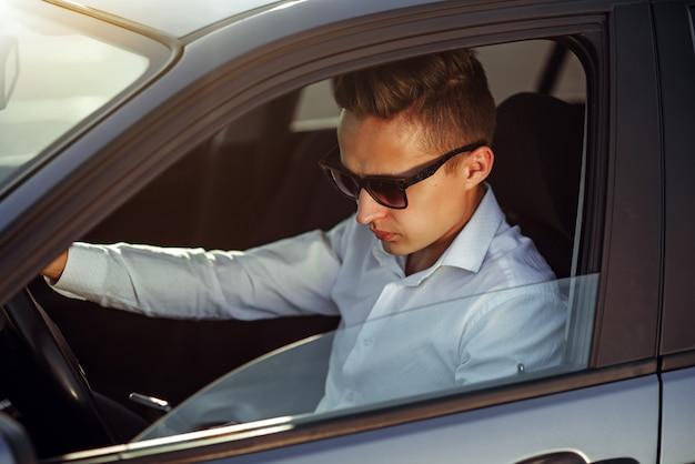 Atrakcyjny przystojny mężczyzna w okularach przeciwsłonecznych używać mądrze telefon w jego samochodzie