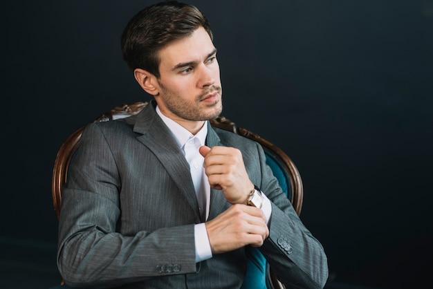 Atrakcyjny przystojny młodego człowieka obsiadanie na rocznika krześle przeciw czarnemu tłu